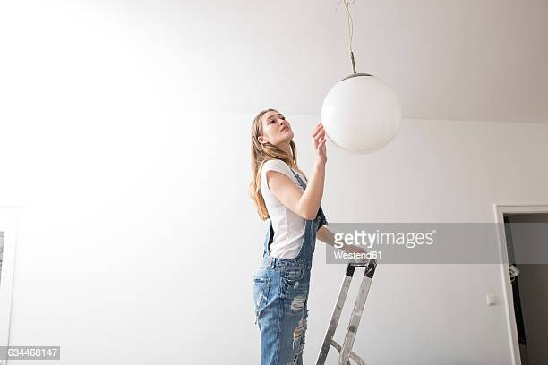 Young woman standing on a ladder checking ceiling light