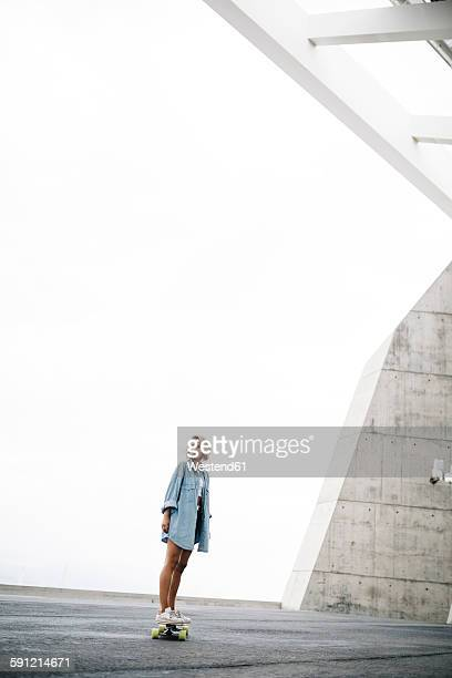 Young woman standing on a longboard
