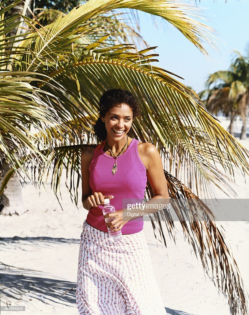 Young Woman Standing on a Paradise Beach Holding a Bottle of Drinking Water : Stock Photo