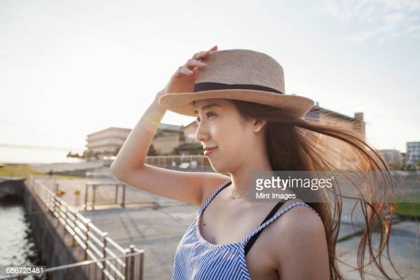Young woman standing on a pier by water holding her straw hat on her head.