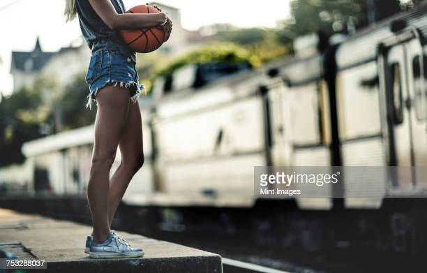 young woman standing on a railway station platform holding a basketball, with a train behind. - blonde long legs stock pictures, royalty-free photos & images