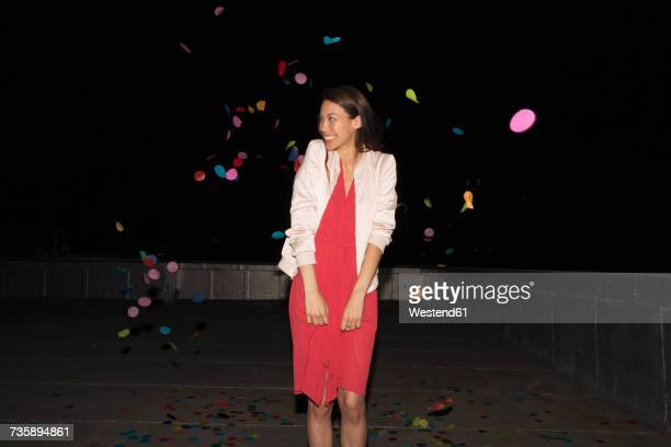 young woman standing on a rooftop terrace with flying confetti - flying solo after party bildbanksfoton och bilder
