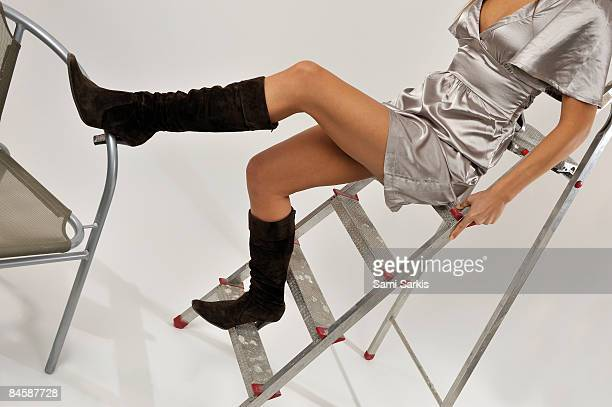 Young woman standing on a step ladder