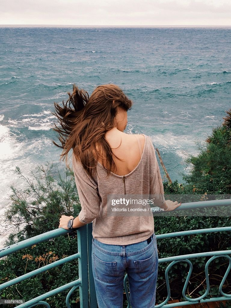 Young Woman Standing On Balcony By Sea : Foto stock