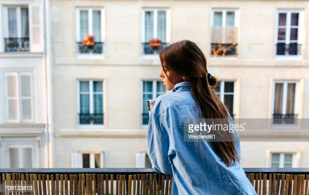Young woman standing on balcony, holding cup of coffee