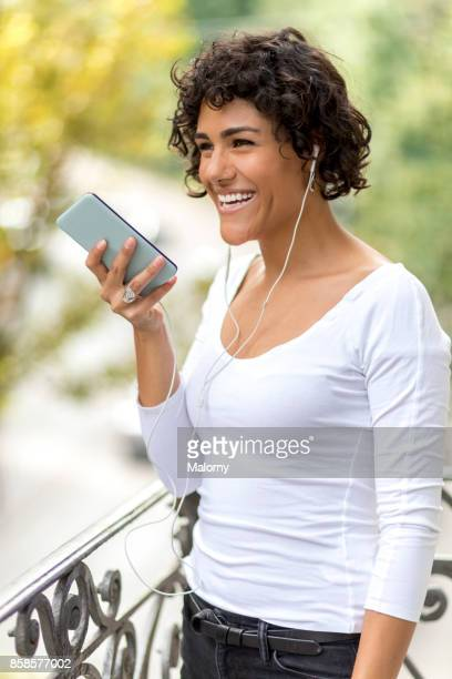 Young woman standing on balcony sending a voice mail on her smart phone. Alt: Talking on the phone