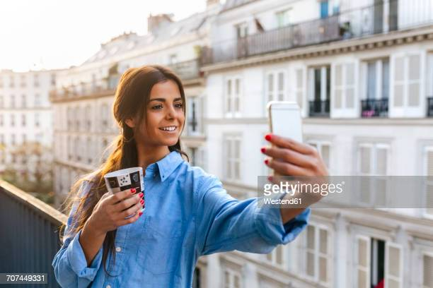 Young woman standing on balcony takinf smart phone selfie