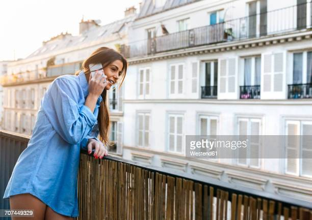 Young woman standing on balcony talking on the phone
