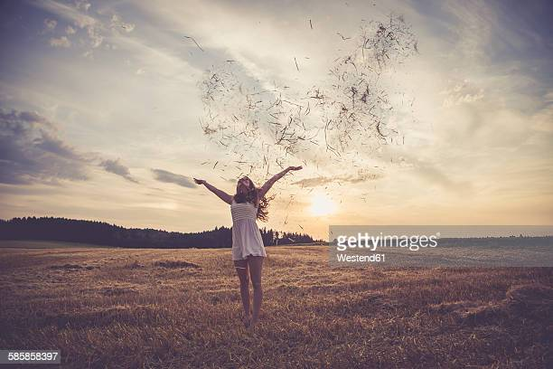 Young woman standing on barley field, throwing straw