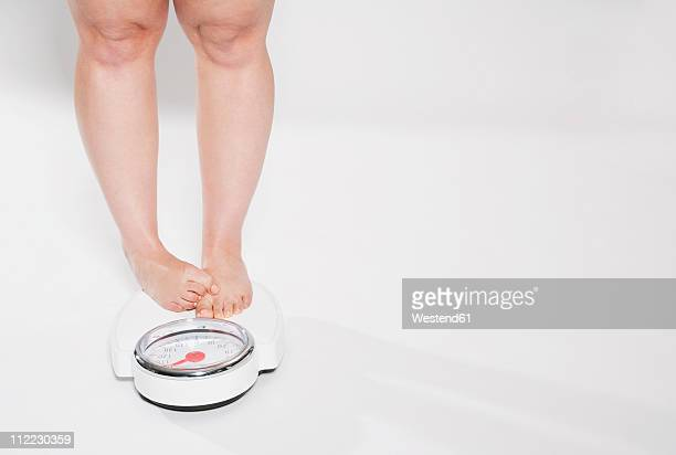 young woman standing on bathroom scales - chubby legs stock photos and pictures