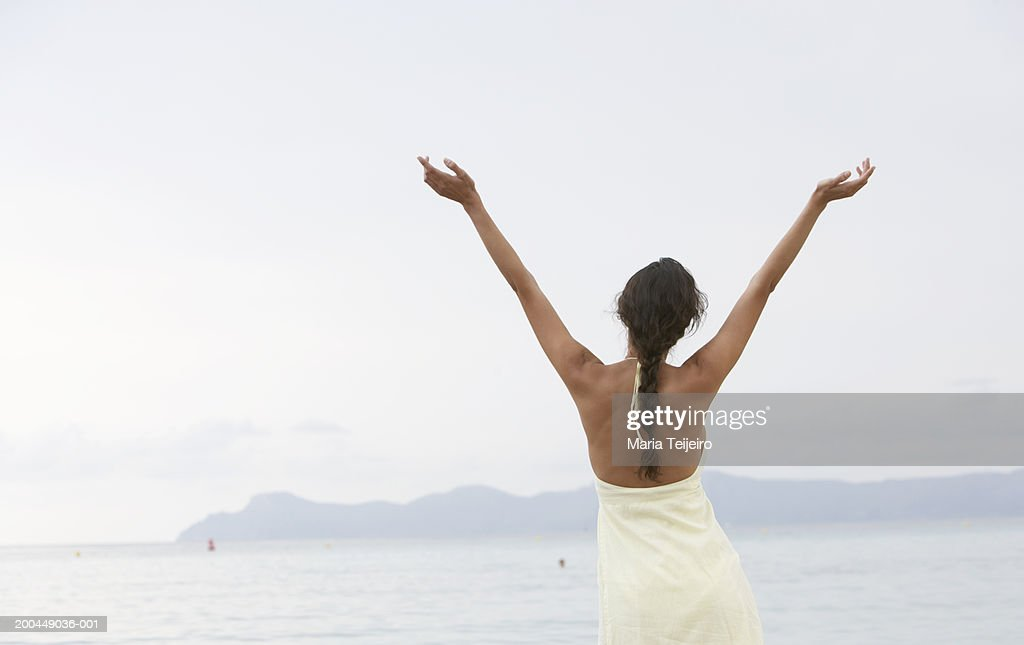 Young woman standing on beach, arms raised, rear view : Stock Photo