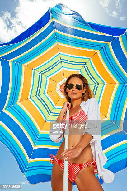 Young woman standing on beach holding a parasol