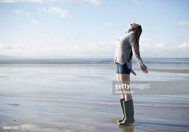 young woman standing on beach looking up, brean sands, somerset, england - sean malyon stock pictures, royalty-free photos & images