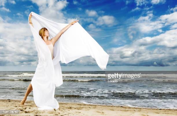 Jeune femme debout sur la plage avec un tissu blanc