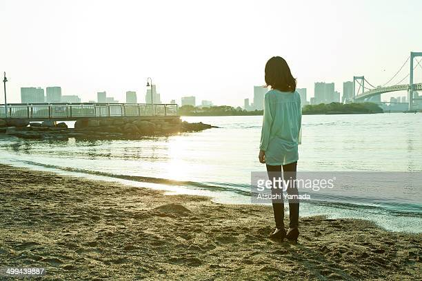Young woman standing on beach,rear view