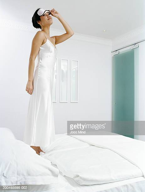 Young woman standing on bed, wearing nightwear, lifting up sleep mask
