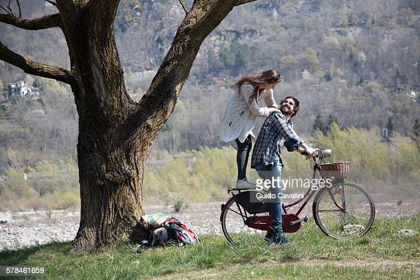 Young woman standing on bicycle behind boyfriend