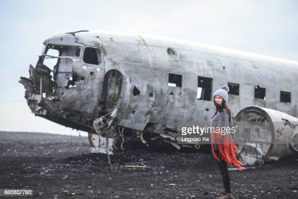 Young woman standing on black beach with Plane Wreck, Vik, Iceland