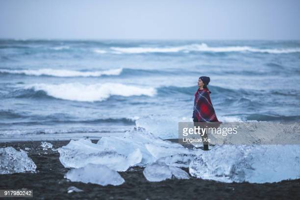Young woman standing on black sand beach near Jökulsárlón Glacier Lagoon, Iceland