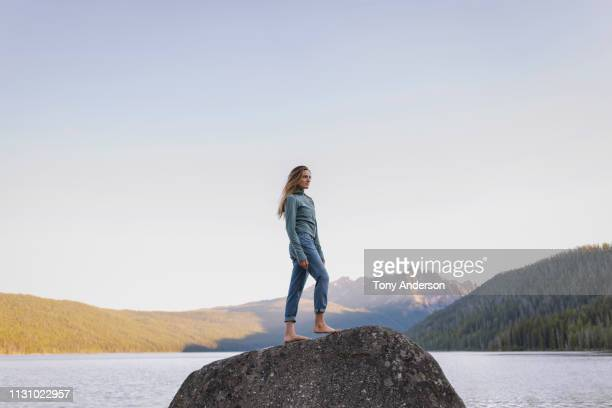 young woman standing on boulder looking at mountain lake - デニム ストックフォトと画像