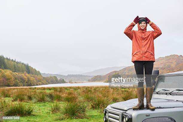 young woman standing on car in landscape - gummistiefel frau stock-fotos und bilder