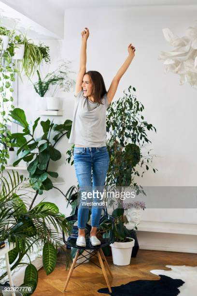 young woman standing on chair in a room cheering - houseplant stock pictures, royalty-free photos & images
