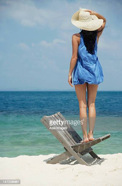 young woman standing on chair looking at ocean