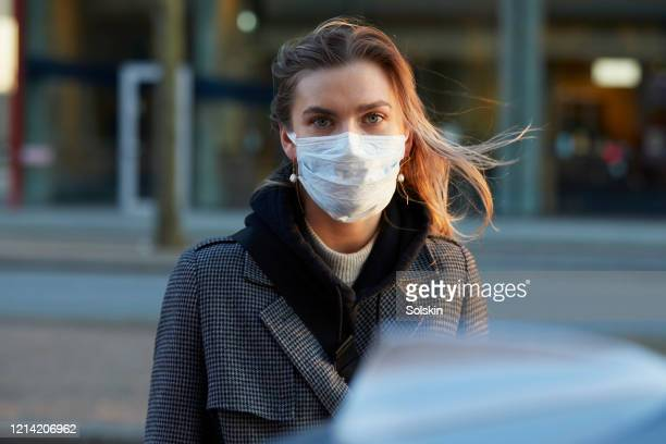 young woman standing on city street wearing protective face mask - grippeschutzmaske stock-fotos und bilder
