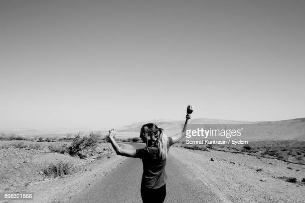 Young Woman Standing On Desert Against Clear Sky