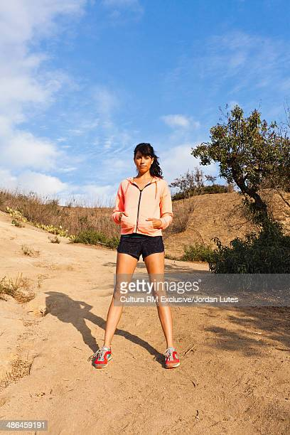 Young woman standing on dirt track wearing shorts