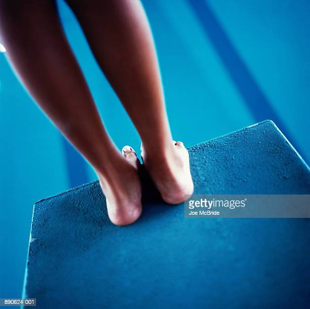 Young woman standing on diving board, low section