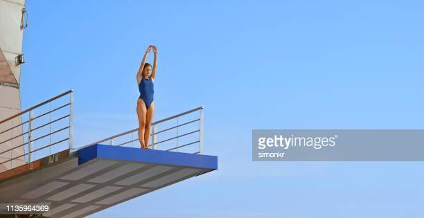 young woman standing on diving board - diving platform stock pictures, royalty-free photos & images
