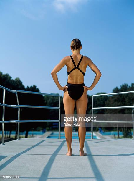 Young woman standing on diving platform