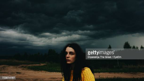young woman standing on field - ominous stock photos and pictures