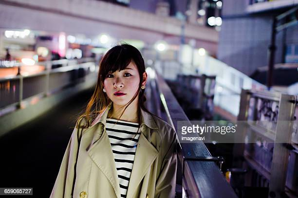 Young woman standing on footbridge at night