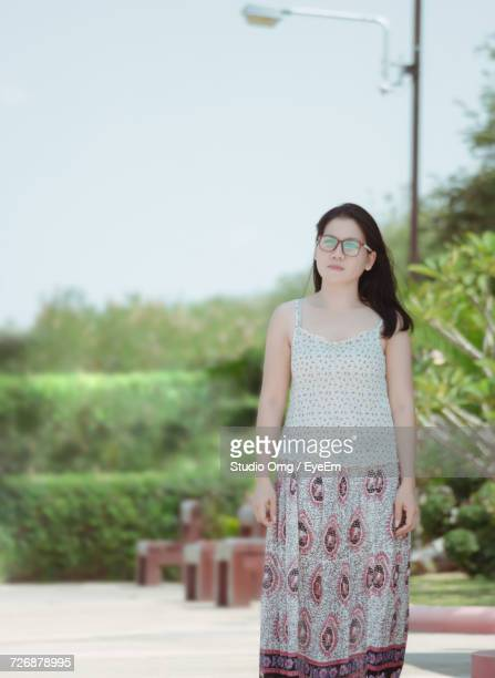 Young Woman Standing On Footpath At Park