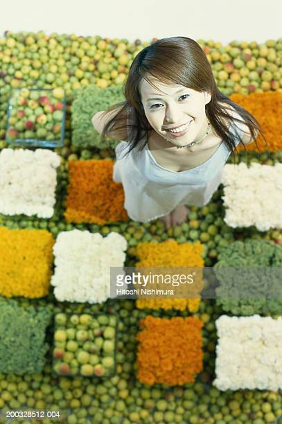 Young woman standing on fruits and flowers, looking up, elevated view