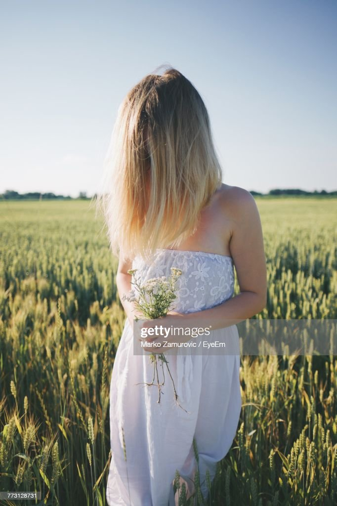 Young Woman Standing On Grassy Field Against Clear Sky : Photo