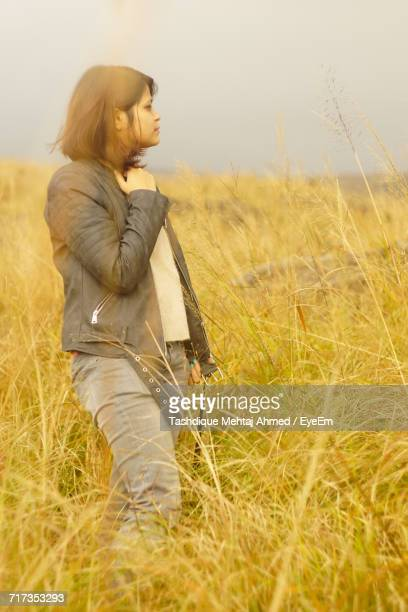 Young Woman Standing On Grassy Field Against Sky