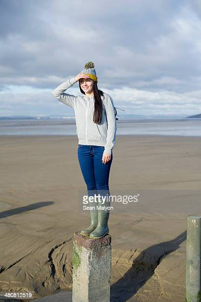young woman standing on groynes, brean sands, somerset, england - sean malyon stock pictures, royalty-free photos & images