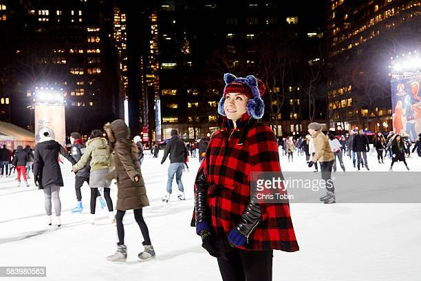 young woman standing on ice skating rink in city - ice rink stock photos and pictures