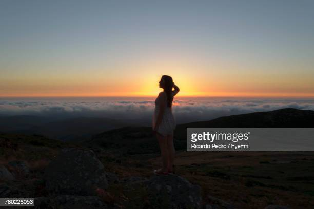 young woman standing on landscape against sky during sunset - モンシケ ストックフォトと画像