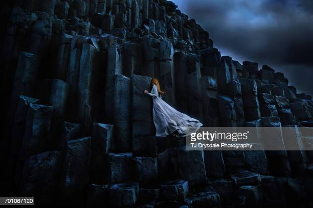 Young woman standing on large basalt rocks in Iceland, looking away
