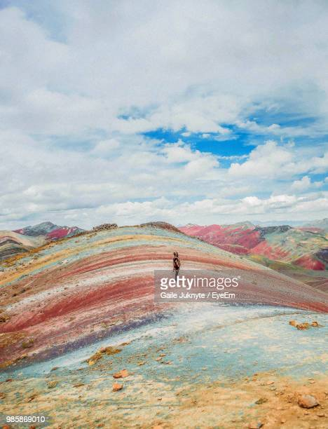 young woman standing on mountain against cloudy sky - perù foto e immagini stock
