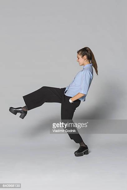 Young woman standing on one leg against gray background