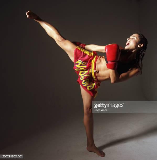 Young woman standing on one leg kick boxing