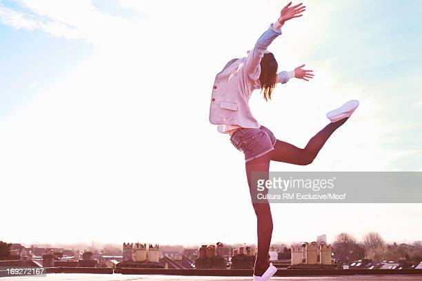 Young woman standing on one leg on roof terrace
