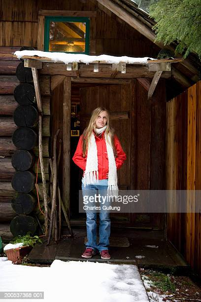 Young woman standing on porch of log cabin, hands in pockets