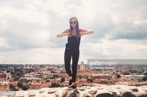 Young Woman Standing On Retaining Wall At Vilnius Old Town Against Sky