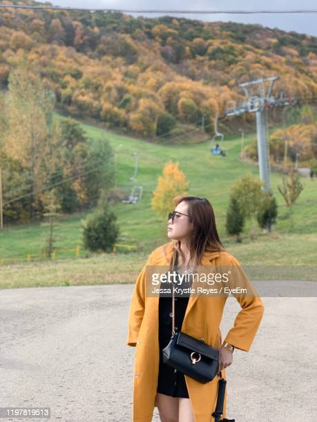 young woman standing on road against mountain - jessa stock pictures, royalty-free photos & images